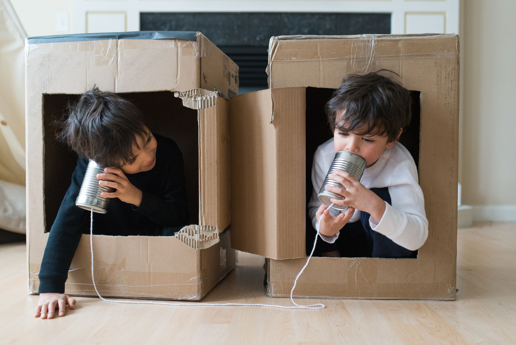 little boys playing telephone in fort